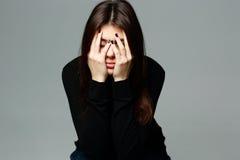 La mujer joven deprimida con entrega su cabeza Imagenes de archivo
