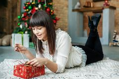 La mujer joven desempaqueta la caja de regalo Año Nuevo del concepto, Feliz Navidad, Imágenes de archivo libres de regalías