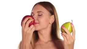 La mujer joven desnuda lleva el lápiz labial rojo y tiene su pelo abajo, y cepillado, comiendo una manzana grande, rojo oscuro y  almacen de metraje de vídeo