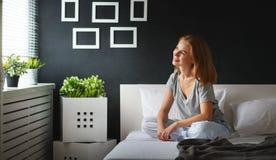 La mujer joven despertó por la mañana en el dormitorio por el windo Fotografía de archivo