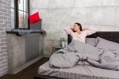 La mujer joven despertó y estirando mientras que se sentaba en la cama y Imagen de archivo