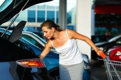 La mujer joven desplaza la compra del carro de la compra en el tronco Imagenes de archivo