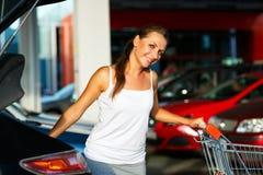 La mujer joven desplaza la compra del carro de la compra en el tronco Fotografía de archivo