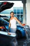 La mujer joven desplaza la compra del carro de la compra en el tronco Fotografía de archivo libre de regalías
