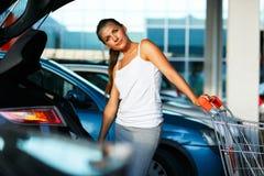 La mujer joven desplaza la compra del carro de la compra en el tronco Imagen de archivo