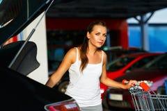 La mujer joven desplaza la compra del carro de la compra en el tronco Fotos de archivo