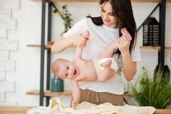 La mujer joven detiene a su bebé al revés fotografía de archivo