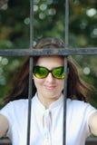 La mujer joven detrás de una protección del hierro Foto de archivo