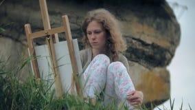 La mujer joven dibuja en las pinturas del caballete y el puente viejo del vintage del cepillo metrajes