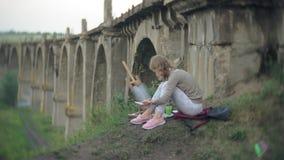 La mujer joven dibuja en las pinturas del caballete y el puente viejo del vintage del cepillo almacen de metraje de vídeo