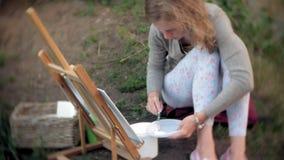 La mujer joven dibuja en las pinturas del caballete y el puente viejo del vintage del cepillo almacen de video