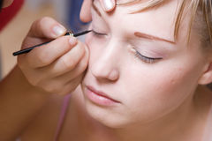 La mujer joven dirige un maquillaje por la mañana fotos de archivo