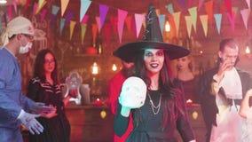 La mujer joven disfrazada en traje de la bruja sostiene un cráneo en sus manos en un partido de Halloween almacen de video