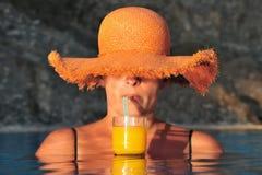 La mujer joven disfruta de la bebida fresca en piscina fotografía de archivo libre de regalías