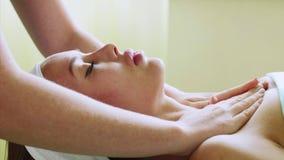 La mujer joven disfruta de masaje facial en salón del balneario de la belleza en el tratamiento de la salud almacen de metraje de vídeo