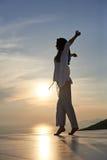 La mujer joven disfruta de puesta del sol Imagenes de archivo