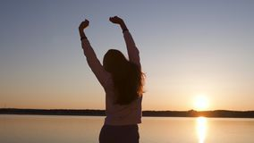 La mujer joven disfruta de puesta del sol durante hora de oro en una playa del r?o en pantalones, sweatshort y chaqueta blancos q almacen de metraje de vídeo