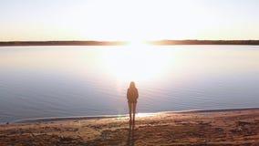 La mujer joven disfruta de puesta del sol durante hora de oro en una playa del r?o en pantalones, sweatshort y chaqueta blancos q almacen de video