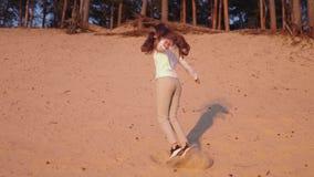 La mujer joven disfruta de puesta del sol en la cámara lenta durante hora de oro en una duna de arena blanca de la playa del río  almacen de video