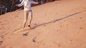 La mujer joven disfruta de puesta del sol en la c?mara lenta durante hora de oro en una duna de arena blanca de la playa del r?o  metrajes