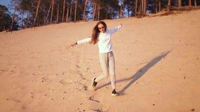 La mujer joven disfruta de puesta del sol en la c?mara lenta durante hora de oro en una duna de arena blanca de la playa del r?o  almacen de metraje de vídeo