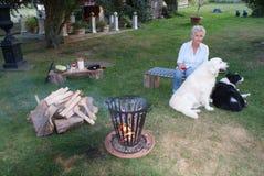 La mujer joven disfruta de la tarde caliente del verano en la hoguera con su golden retriever y border collie y un vidrio de vino foto de archivo libre de regalías