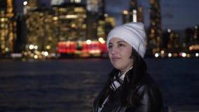 La mujer joven disfruta de la visión fantástica sobre el horizonte de Manhattan por noche almacen de video