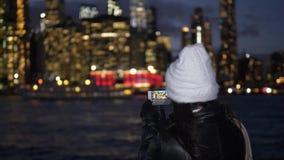 La mujer joven disfruta de la visión fantástica sobre el horizonte de Manhattan por noche almacen de metraje de vídeo