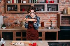 La mujer joven disfruta del aroma de la cocina de la pizza en casa foto de archivo libre de regalías