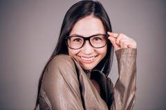 La mujer joven divertida carismática con los vidrios mira la cámara con una sonrisa Emociones, felicidad imagenes de archivo