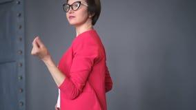 La mujer joven divertida en la chaqueta rosada está bailando y se está divirtiendo aislada sobre negro metrajes
