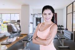 La mujer joven dobló sus brazos en centro del gimnasio imagen de archivo