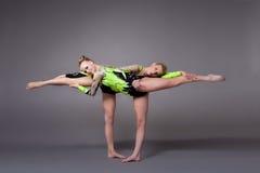 La mujer joven dos como acróbatas ejercita programa de los pares Fotografía de archivo