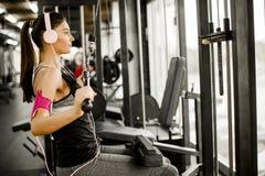 La mujer joven ejercita en una máquina del ejercicio en el listenin del gimnasio imagen de archivo