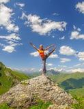 La mujer joven ejercita yoga en las montañas Imágenes de archivo libres de regalías