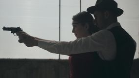 La mujer joven elegante del retrato en el vestido rojo que apunta un arma, hombre galante hermoso se coloca detr?s, dirigiendo su almacen de video