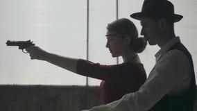 La mujer joven elegante en el vestido rojo que apunta un arma, hombre galante hermoso se coloca detr?s, dirigiendo su mano, vista almacen de video