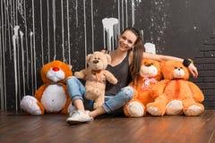 La mujer joven elegante sonriente de la diversión con los juguetes lleva Fotografía de archivo