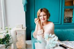La mujer joven elegante vestida hermosa se est? relajando por la ma?ana en un caf? Restaurante interior en colores azules E foto de archivo libre de regalías