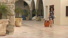 La mujer joven elegante vestida viaja al extranjero para el viaje que hace compras, va al hotel almacen de video