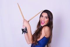 La mujer joven elegante y de moda que sostiene el tambor se pega Fotografía de archivo libre de regalías