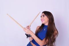 La mujer joven elegante y de moda que sostiene el tambor se pega fotos de archivo
