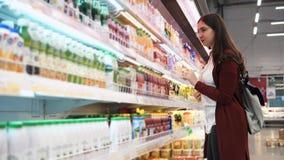 La mujer joven elige bebidas en el colmado, mirando la composición metrajes