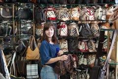 La mujer joven elige el bolso Imagen de archivo