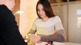 La mujer joven elige el color y la textura de clavos en el salón de belleza profesional de la manicura, resbalador metrajes