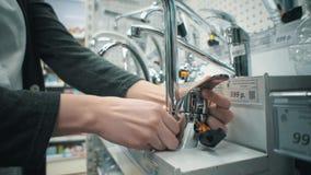 La mujer joven elige el golpecito de mezclador en tienda del autoservicio almacen de video