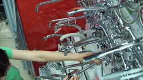 La mujer joven elige el golpecito de mezclador en tienda del autoservicio almacen de metraje de vídeo