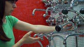 La mujer joven elige el golpecito de mezclador en tienda del autoservicio metrajes