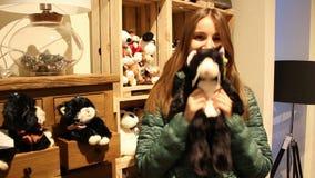 La mujer joven elige el juguete suave del regalo de la Navidad metrajes