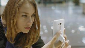 La mujer joven elige el teléfono móvil metrajes